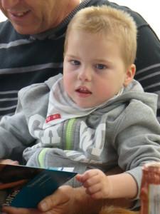 Anthony schaut sich auf dem Schoß seines Opas schon mal ein Buch über Delfine an